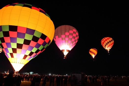 Photo of hot air balloons aglow with dark sky